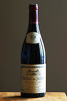 A bottle of Maison Louis Jadot Bourgogne Chateau des Jacques Moulin-a-Vent Beaujolais red burgundy wine standing on a wooden table top. Backlit backlight back light lit. gray grey background sidelit side light, Maison Louis Jadot, Beaune Côte Cote d Or Bourgogne Burgundy Burgundian France French Europe European
