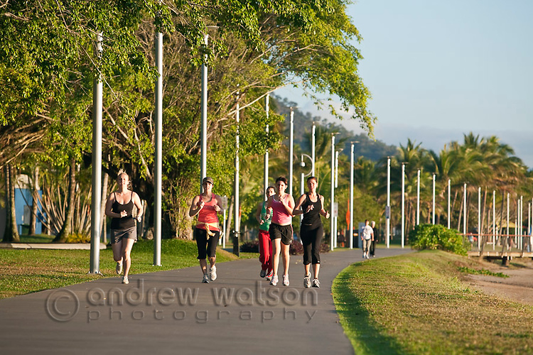 Early morning joggers on the Esplanade.  Cairns, Queensland, Australia