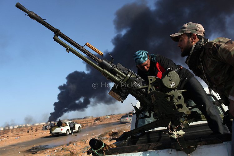 Opposition fighters reload an anti-aircraft canon in front of thick plume of smoke from a nearby oil refinery in Ras Lanuf, Libya, March, 11, 2011. Loyalist forces of Col. Muammar Qaddafi pushed rebels back from the strategic oil town with air strikes, artillery and small arms fire.