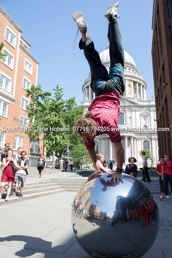 London, UK. 21.06.2014. Belarus Free Theatre, in conjunction with Parkour Generations, stage a protest event, to coincide with their production of RED FOREST at the Young Vic theatre. After the explosion at Chernobyl in 1986, the forest turned red. The event was to highlight that air and water supplies today are under attack from dangerous and dirty forms of energy production. Picture shows: Jacob Peregrine-Wheller in front of St Paul's Cathedral. Photograph © Jane Hobson.