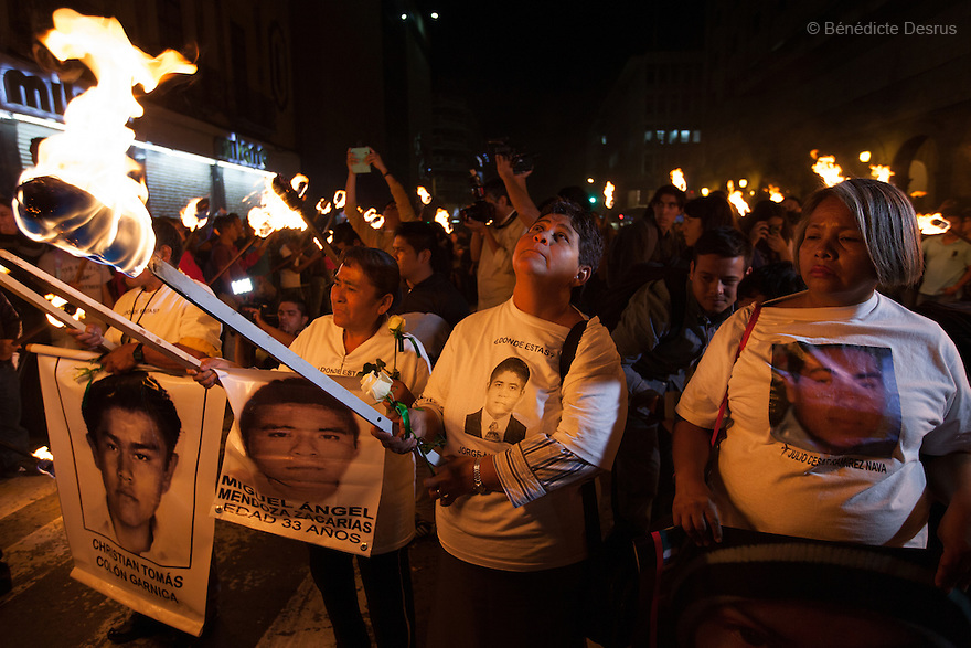 Parents and classmates of the 43 missing students from Ayotzinapa's teacher training college hold 43 torches and images of the missing students during a march in Guadalajara, Jalisco, Mexico on November 18, 2014. The relatives of the 43 missing students still do not believe the official line that the young men are all dead, and with classmates, social organizations and human rights defenders, they started on Thursday a national caravan. They split up into three different caravans, branching out to share information face to face with supporters in other cities and rally nationwide support. The three groups will meet in Mexico City on Thursday 20 for a general strike and massive marches to demand justice and fight against corrupted government and organized crime. Criticism of the government has intensified in Mexico, and many are demanding that the search for the 43 missing students continue until there is concrete evidence to the contrary. (Photo by BénédicteDesrus)