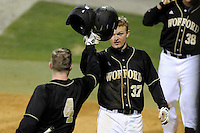 First baseman James Plaisted (37) of the Wofford College Terriers is congratulated by teammates after scoring a run in a game against the Boston College Eagles on Friday, February 13, 2015, at Russell C. King Field in Spartanburg, South Carolina. Wofford won, 8-4. (Tom Priddy/Four Seam Images)