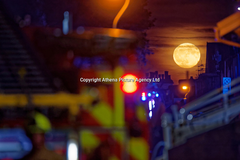 Pictured: A full moon seen rising over rooftops In Carlton Terrace, near at the scene of a fire in Swansea, Wales, UK. Wednesday 24 October 2018<br /> Re: Firefighters are battling a fire in Swansea, Wales, UK.<br /> The fire is in a back lane running parallel between Carlton Terrace and Mansel Street in the Mount Pleasant area.<br /> South Wales Fire and Rescue Service have confirmed that they are in attendance at the scene.