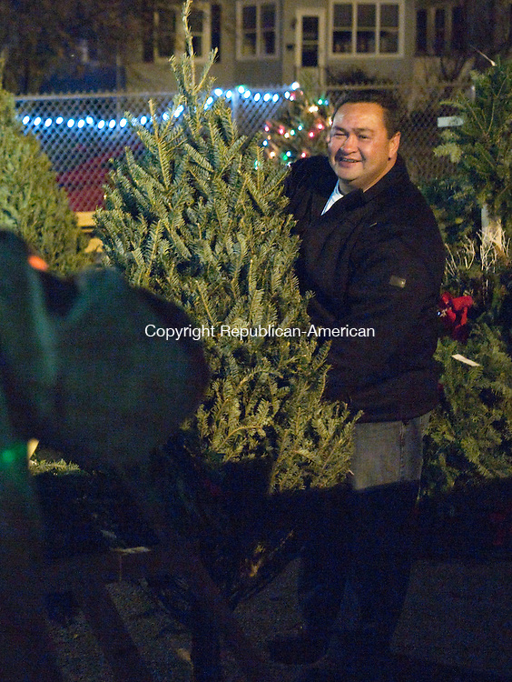 Waterbury, CT- 30 November 2015-113015CM04- Bart Cammarasana, right, helps a customer with a Christmas tree at Saints Peter and Paul School in Waterbury on Monday.  Cammarasana who is the co-president of the fundraiser said ten Christmas trees were stolen from the school.      Christopher Massa Republican-American