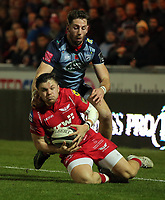 Steffan Evans of the Scarlets (FRONT) grabs the ball from the ground while closely followed by Alex Cuthbert of Cardiff Blues during the Guinness PRO14 match between Scarlets and Cardiff Blues at Parc Y Scarlets Stadium, Llanelli, Wales, UK. Saturday 28 October 2017