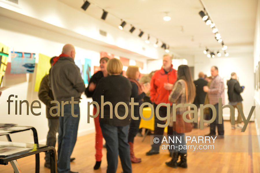 Huntington, New York, U.S. - March 1, 2014 - The Opening Reception '3 Wild and Crazy Artists' at FotoFoto Gallery, seen through front window, presents fine art photography works, including, at left,  'Hung Out to Dry' exhibit by Thom O'Connor.