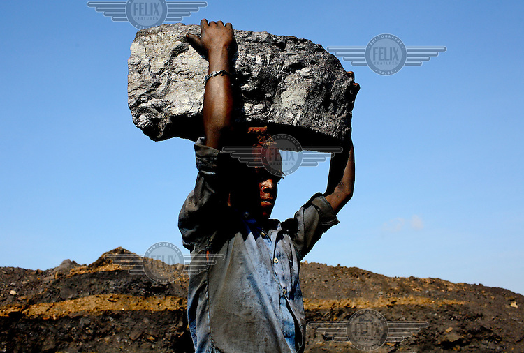 A young man scavenging coal carries, on his head, a great block of the rock that he has taken illegally from an open-cast mine near the village of Bokapahari where a community of coal scavengers live and work. /Felix Features