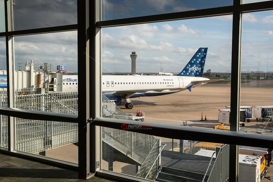 View looking out of the terminal window of an jet airplane parked at the airport gate overshadowed by the airport traffic control tower at Austin–Bergstrom International Airport - Stock Image.