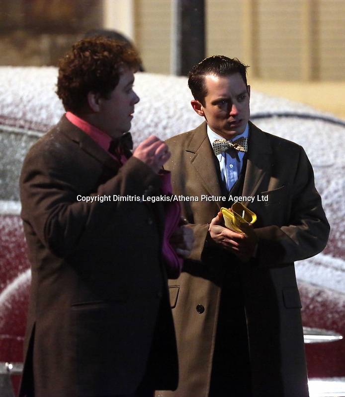 Pictured L-R: Celyn Jones and Elijah Wood warm up his hands with hot water bottles. Tuesday 11 February 2014<br /> Re: A Swansea street was transformed into 1950s New York for new Dylan Thomas biopic 'Set Fire to the Stars' starring Holywood actor Elijah Wood.<br /> Gloucester Place in Swansea Marina was used to film a snowy scene in New York.<br /> Half a dozen 50s American cars were used for the scene played by Elijah Wood and Celyn Jones.<br /> The new movie will explore the fractious relationship between Dylan Thomas played by Jones and John Malcolm Brinnin played by WOod, who brought the Welshman to the USA and acted as his tour agent.