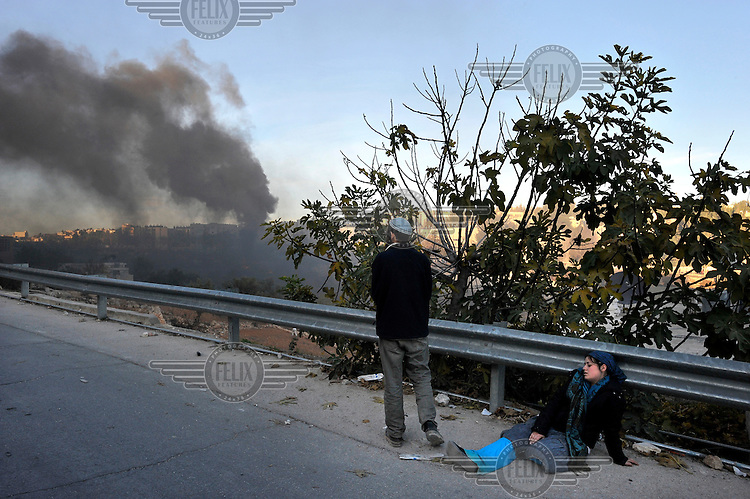 Smoke rises as Jewish settlers riot after the Israeli army evicted a group of settlers from a disputed building in Hebron. As a settler woman lies exhausted, a man looks back at the scene. The Israeli high court had rejected the settlers' claim that they legally bought the house from its Palestinian owner. As the house became a symbol of defiance, the few families living there were joined by a mob of some 1,500 radical right-wing youths, who went on a rampage and attacked Palestinians in the mixed West Bank city.