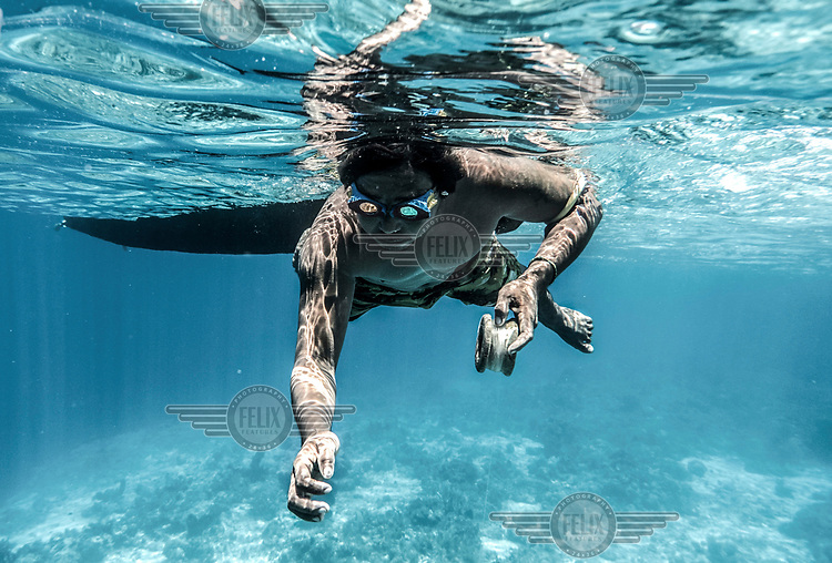 Marjono Lessing (35) dangles an octopus lure Kabalutan in Indonesia's Togean islands. Octopus is one of the main sources of income for the Bajau.
