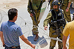 An Israeli army officer declares the area a closed military zone as Palestinian protesters attempt to remove a road block during a demonstration against Israel's controversial separation barrier in the West Bank town of Beit Jala near Bethlehem on 04/07/2010.