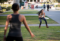 Occidental College students Sirena Van Epp '15 (in white top) and Jenny Wang '14 (gray top) take a break from studying for finals to play catch with a flying disc (frisbee) on Dec. 11, 2013 in the Academic Quad. (Photo by Marc Campos, Occidental College Photographer)
