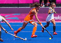 29 JUL 2012 - LONDON, GBR - Naomi van As (NED) of Netherlands (centre) makes her way upfield during the women's London 2012 Olympic Games Preliminary round hockey match against Belgium at the Riverbank Arena in the Olympic Park in Stratford, London, Great Britain (PHOTO (C) 2012 NIGEL FARROW)