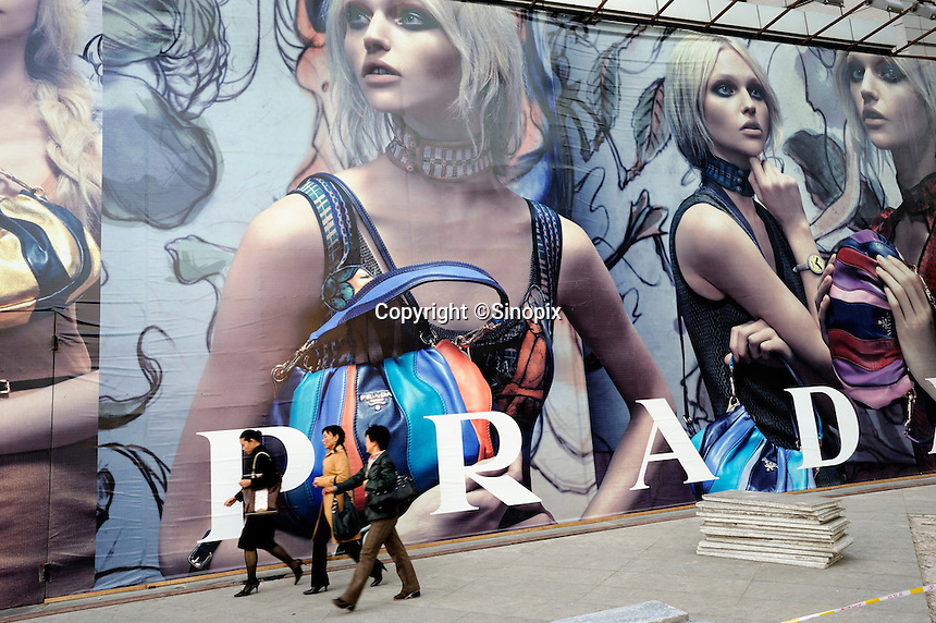 Chinese ladies walk past a huge Prada billboard at Shin Kong Place, which is one of the most luxurious shopping centers in Beijing, having successfully attracted 938 international class brands, they also boast the largest Gucci flagship store in Asia..