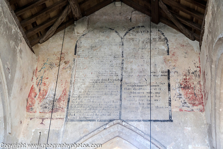 Building interior medieval church architectural feature, Inglesham, Wiltshire, England decalogue of 19th century prayer overlain on many layers of medieval paintings on chancel wall