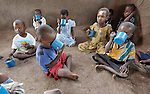 "Children eat porridge in a care center for orphans and other vulnerable children in Chidyamanga, a village in southern Malawi that has been hard hit by drought in recent years, leading to chronic food insecurity, especially during the ""hunger season,"" when farmers are waiting for the harvest. The ACT Alliance is working with farmers in this village to switch to alternative, drought-resistant crops, as well as using irrigation and other improved techniques to increase agricultural yields. In Chidyamanga, residents have set aside a section of farmland where they work together to grow food especially for the orphans--many of whom lost their parents to AIDS--and other children in the center. Three times a week, the children come to the center, sing and play and eat a nutritious meal."