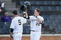 Will Craig (22) of the Wake Forest Demon Deacons bumps helmets with teammate Evan Stephens (5) after hitting a 3-run home run in the bottom of the first inning against the High Point Panthers at Wake Forest Baseball Park on April 2, 2014 in Winston-Salem, North Carolina.  The Demon Deacons defeated the Panthers 10-6.  (Brian Westerholt/Four Seam Images)