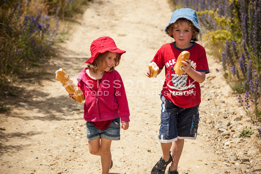 Children (girl 4 years boy 6 years) walking and eating bread along a track, New Zealand - stock photo, canvas, fine art print