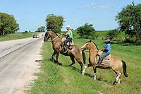 URUGUAY Salto, Gauchos ueberqueren eine Strasse /<br /> URUGUAY Salto, Gauchos on horse cross a road