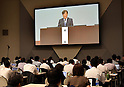June 24, 2016, Makuhari, Japan - Reporters take notes as Chairman Osamu Mashiko, on the monitor, of the trouble-stricken Mitsubishi Motors addresses a general stockholders meeting at Makuhari Messe, east of Tokyo, on Friday, June 24, 2016. The Japanese automaker forecast its first loss in eight years after setting aside compensation costs related to manipulating fuel-efficiency ratings and falsifying test data. Net loss in the year ending March 31 will probably be $1.4 billion, the company said in a statement Wednesday.  (Photo by Natsuki Sakai/AFLO) AYF -mis-