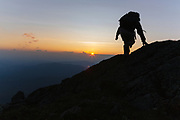 A hiker travels along the Appalachian Trail at sunset near Moun Washington in the White Mountains, New Hampshire USA.