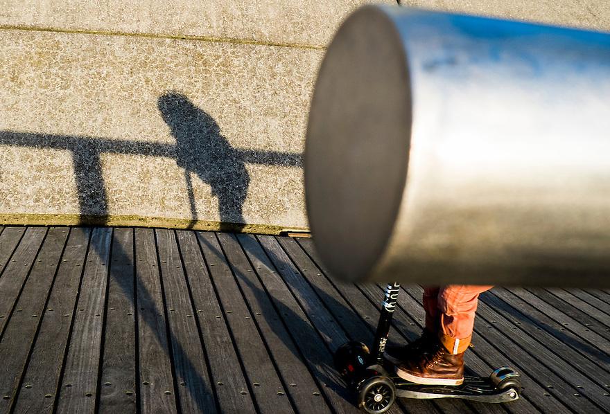 Nederland, Rotterdam, 12 jan 2014<br /> Kop van Zuid. Kind op een stepje is verscholen achter een leuning, maar z'n schaduw is wel zichtbaar.<br /> <br /> Foto: Michiel Wijnbergh
