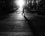 A silhouetted person crossing the street in bright light
