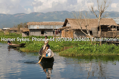 Inle Lake. Myanmar (Burma.) 2006. Young children playing in their boats village behind.