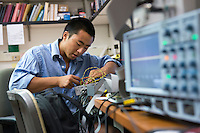 "Kevin Kuwata '15, after pulling an all-nighter, works on his project, ""Commissioning of Drift II-e Detector"" as part of Occidental College's Summer Research Program, summer 2013. (Photo by Marc Campos, Occidental College Photographer)"