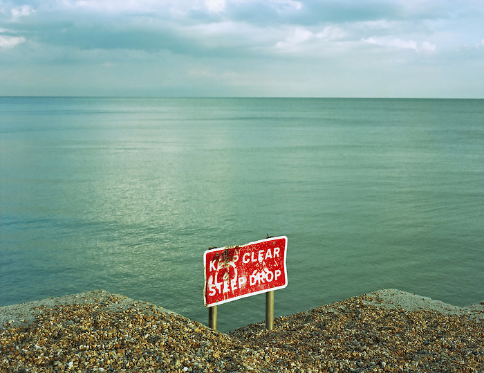 A sign on a groyne - breakwater - warns of a steep drop onto a lower section of beach on the shore of Brighton beach on the South coast of England.<br />