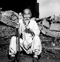 An old Korean man takes a rest on the street in front of destroyed buildings, in Seoul.  August 20, 1951.  G. Dimitri Boria.  (Army)<br /> NARA FILE #:  111-C-6787<br /> WAR & CONFLICT BOOK #:  1483