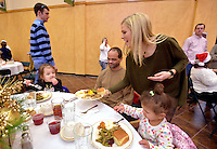 STAFF PHOTO BEN GOFF  @NWABenGoff -- 12/25/14 Maggie Kell, a church member and volunteer, serves Leslie Alley of Rogers and his daughters Trinity Alley, 3, left, and Sunni Alley, 2, during the annual Christmas meal for the community at Central United Methodist Church in Rogers on Thursday Dec. 25, 2014. The church and volunteers from the community also offer take out dinners and delivery for homebound individuals on Christmas.
