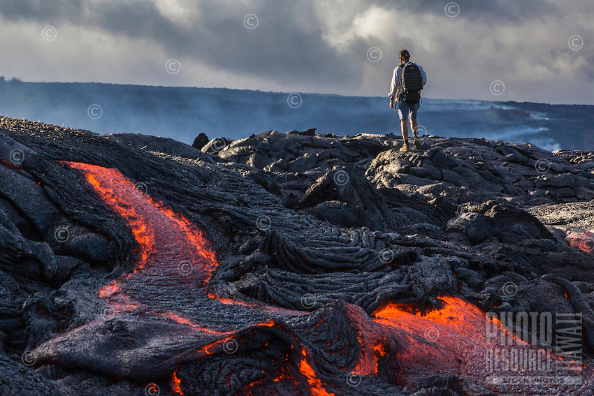 A man who hiked through lava fields pauses to take in his reward:  a view of new lava flow, Hawai'i Island.