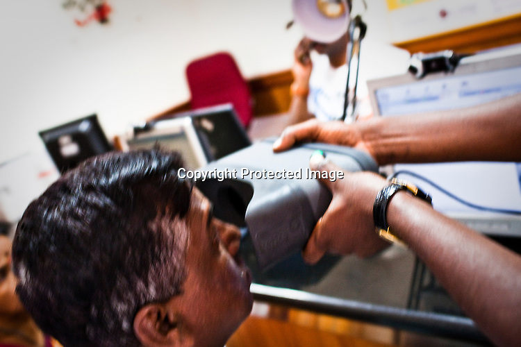 An assistant helps place the iris scanner during national identity enrolment, a resident is seen having his iris scanned in Mysore city in Karnataka. Photograph: Sanjit Das/Panos