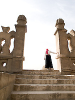 A young lady in her first trip to the Mosque of Ahmed Ibn Tulun explores at the end of the top of the stairs and gazes at the mosque and the city. Cairo, Egypt. Year: 2009.