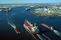 Aerial view of the Houston Ship channel, with a cargo ship and barges underway and refineries lining the banks. Houston, Texas.