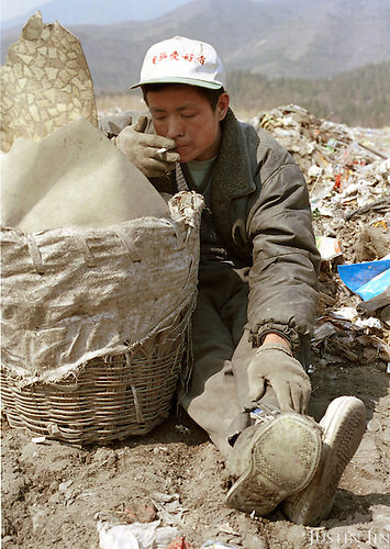 Xu, 25, smokes during a rest at the garbage dump. Xu was planning to return to Sichuan in the summer to find work as a hair dresser. ..Between 50-100 Chinese from a small village in southwestern China's Sichuan province live and work here, one thousand miles away from home. They are part of a cooperative selling scraps and wastes to local farmers and factories...They look for bits of wire, bottles and plastics that they can re-sell. They earn about 300 yuan (US$36) a month per person, which is low by urban standards but is about 10 times as much as wages at home in Sichuan...Picture taken March 1999.Copyright Justin Jin