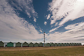 Brighton and Hove, England. Colourful beach huts with a big blue sky and white clouds.