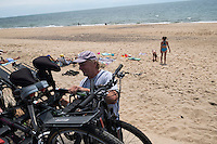 Scott Marble packs up his family's bikes after a day at the beach at Herring Cove Beach in the Cape Cod National Seashore outside of Provincetown, Mass., USA, on Fri., July 1, 2016. Marble's dog Daisy is seen at left. Portions of the parking lot have been closed after land eroded during storms earlier this year. The Marble family spends their summers in Orleans, Mass., on Cape Cod, and the rest of the year in Medfield, Mass. Scott is 60 years old and says he's been coming to the beach for at least 40 years.