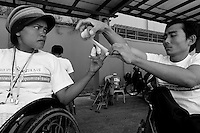 The athletes are putting band around their fingers to protect them from the spokes of the wheels. Kompong Cham, Cambodia - 2009