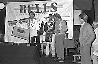 Alan Green, founder of Quiksilver and Alan Atkins after present Joe Engle (AUS) the first surfer to win both the Quiksilver Trials and the Rip Curl Pro, with his Quiksilver Trials award. circa 1983.  Harry Hodge (AUS) looks on. Photo: joliphotos.com.