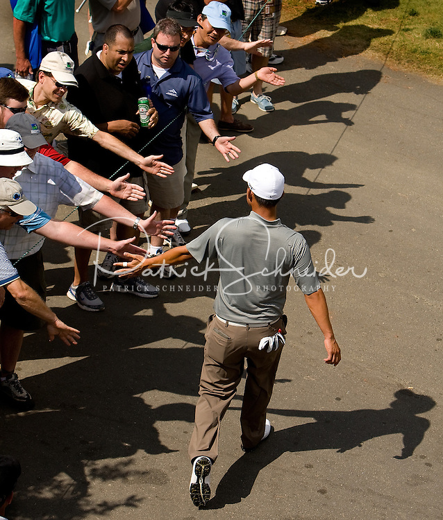 PGA golfer Anthony Kim high fives fans as he walks to a tee box during the 2008 Wachovia Championships at Quail Hollow Country Club in Charlotte, NC.