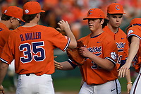 Starting pitcher Jacob Hennessy (32) of the Clemson Tigers is congratulated by Ryan Miller after a scoreless inning in a game against the William and Mary Tribe on February 16, 2018, at Doug Kingsmore Stadium in Clemson, South Carolina. Clemson won, 5-4 in 10 innings. (Tom Priddy/Four Seam Images)