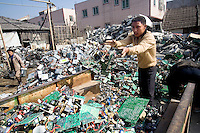 A worker packs electronic trash on to a small truck in order to transport it for processing.
