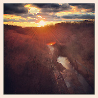 The sun descends toward the horizon over Lincoln Drive and the Wissahickon Creek as see from the Henry Avenue Bridge in Philadelphia December 18, 2012.