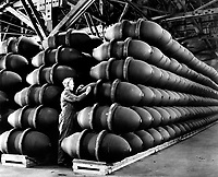 A woman war worker checks over 1,000 pound bomb cases before they are filled with deadly charges of explosives and shipped off to Allied bases and battlefronts all over the world.  Firestone Tire and Rubber Co.  Omaha, NE, ca.  May 1944. Acme.  (OWI)<br /> Exact Date Shot Unknown<br /> NARA FILE #:  208-AA-352AA-5<br /> WAR & CONFLICT BOOK #:  817