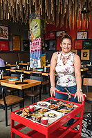 Owner of Super Mega Bien restaurant Dana Rodriguez with her food cart in Denver, Colorado, Thursday, June 15, 2018. Some items on the cart include: tempura-fried squash blossoms stuffed with vanilla-laced Haystack Mountain goat cheese, blue corn and bean gordita topped with a fried quail egg and avocado sauce, pepitas, and a fruit-studded Jell-O dessert dim sum, a take on Peruvian purple corn pudding.<br /> <br /> Photo by Matt Nager