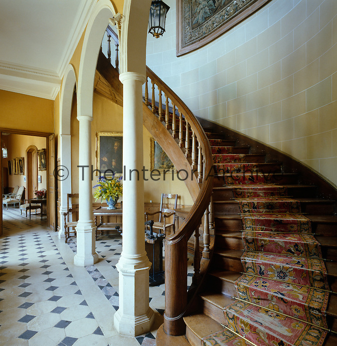 The elegant curved wooden staircase ascends gracefully from the stone-flagged floor of the hall