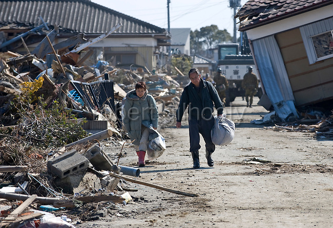 Yoshio Isawa, 60 (R) and his wife Makiko carry personal belongings rescued from their battered home in Tona, Miyagi Prefecture, Japan on  25 March 20011. .Photographer: Robert Gilhooly